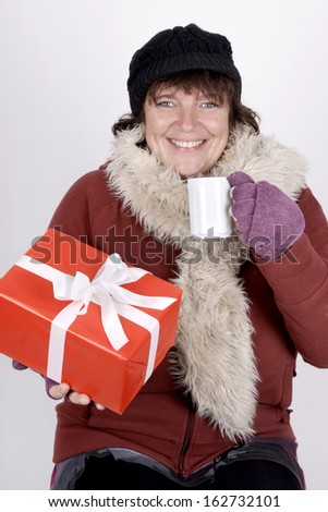 Woman in winter clothes with hot beverage and christmas present - stock photo
