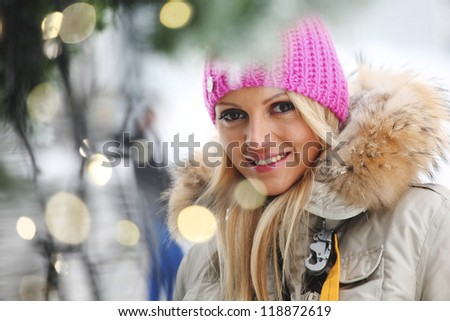 woman in winter hat and holyday bokeh - stock photo