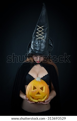 Woman in witch Sexy costume opens carved Halloween pumpkin - stock photo