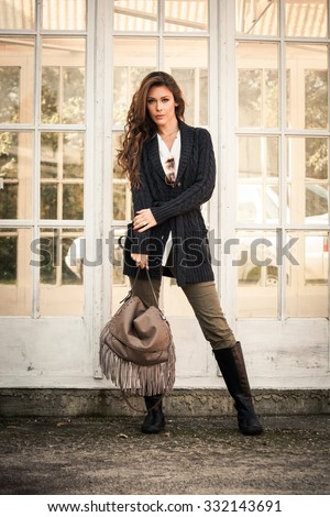 woman in worm dark wool sweater,  black leather high boots hold leather hand bag with tassels stand in front glass door, full body shot - stock photo
