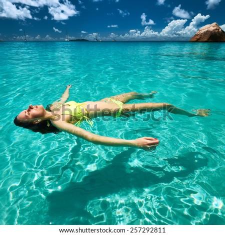 Woman in yellow bikini lying on water at tropical beach - stock photo
