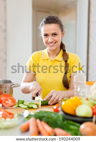 woman in yellow chopping cucumber and other vegetables