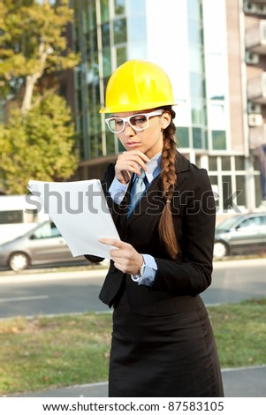 Woman in yellow hard hat,  reading notes while standing - stock photo