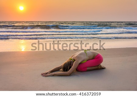 Woman in yoga asana near ocean, sunset time