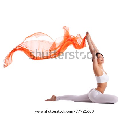 woman in yoga pigeon pose and orange flying fabric