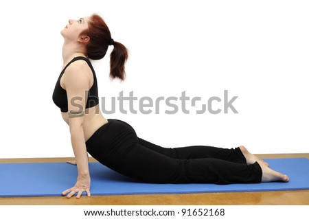 Woman in yoga posture called Upward-Facing Dog on a blue rug, isolated with clipping path.