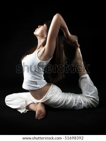 Woman in yoga, the pigeon pose, isolated on black. - stock photo
