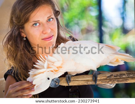 Woman in zoo with parrot of Bali Bird Park, Indonesia - stock photo