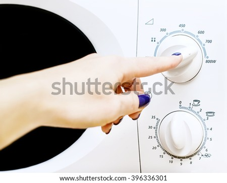 woman includes microwave oven, power and time of microwave ovens - stock photo