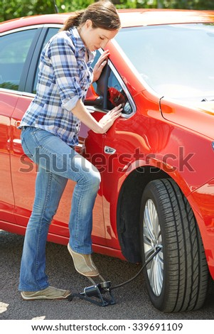 Woman Inflating Car Tyre With Foot Pump