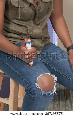 Woman injecting emergency medicine into her leg - stock photo