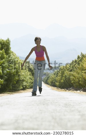 Woman Inline Skating down Concrete Road - stock photo