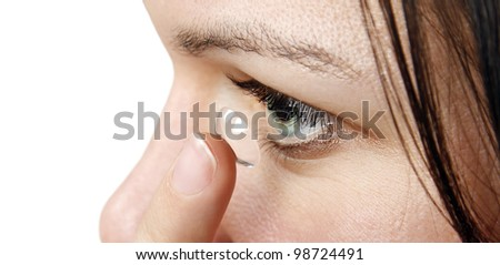 Woman inserting a contact lens - stock photo
