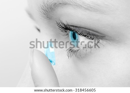 Woman inserting a contact lens in her eye. - stock photo