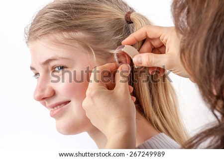 Woman inserting a hearing aid into a young girl's ear in front of a white background - stock photo