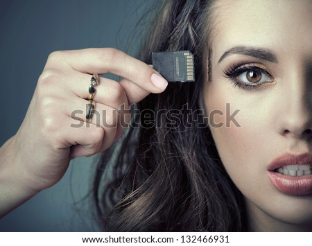 woman inserting card into her head - stock photo