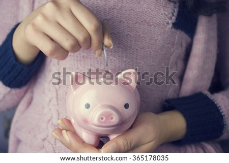 Woman inserting coin in a piggy bank