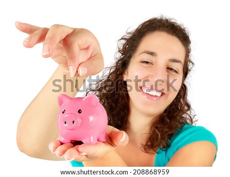 woman inserting coin into piggy bank
