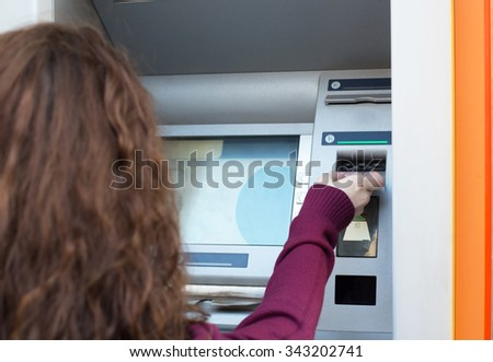 woman inserting credit card to ATM, back view