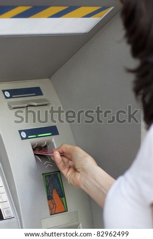 Woman inserts card in the ATM