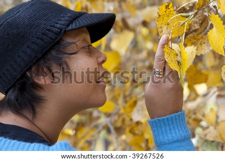 Woman inspecting and enjoying yellow autumn leaves - stock photo