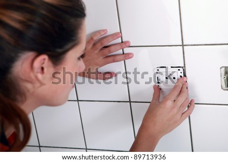 Woman installing electrical socket - stock photo
