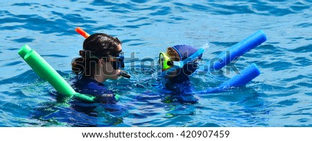 Woman instructor teach little girl how to snorkelling dive in the Great Barrier Reef Queensland Australia - stock photo