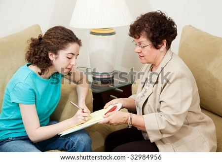Woman interviewing teenage girl asks her to sign paperwork. - stock photo