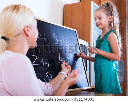 Woman introducing numbers to small girl at home