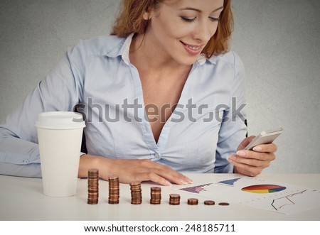 woman investment consultant analyzing company annual financial report balance sheet statement document graph sitting at table with pile of growing coins looking at smart phone. Stock market concept  - stock photo