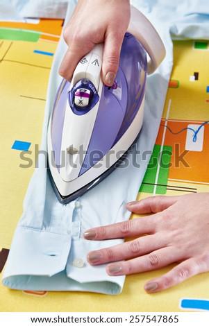 Woman ironed shirt on the ironing board - stock photo