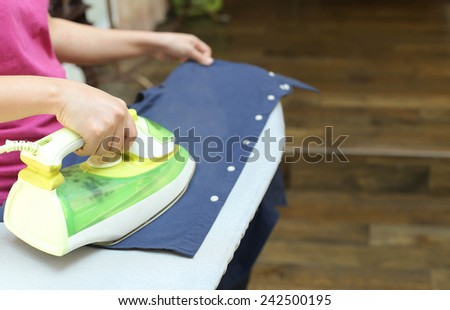 Woman ironing a blue shirt with a steam iron in blur background - stock photo