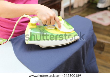 Woman ironing a blue shirt with a steam iron in blur background shirt with a steam iron in blur background - stock photo