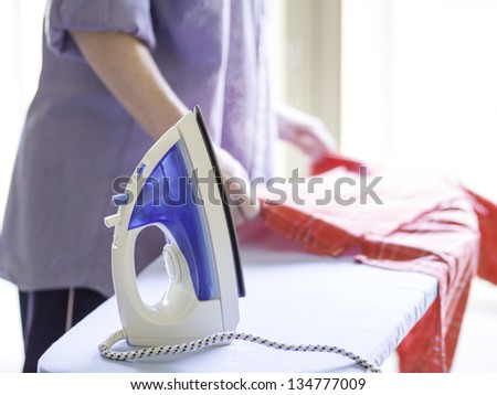 Woman ironing a red shirt with a steam iron taken against a bright, airy background. - stock photo