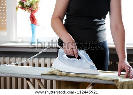 Woman ironing clothes - stock photo