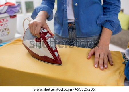 Woman ironing clothing at home - stock photo