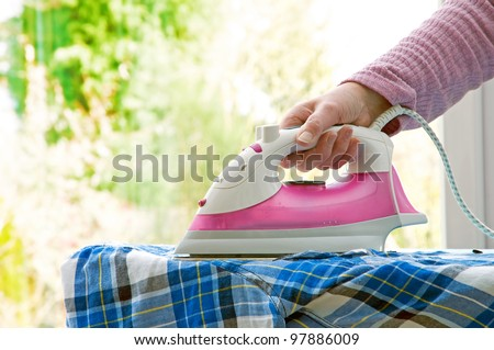 woman ironing shirt with window looking into garden for background - stock photo
