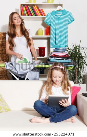 Woman ironing while child is playing - stock photo