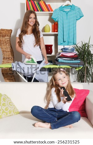 Woman ironing while child is watching TV - stock photo