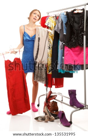 Woman is choosing dresses . She stands near her clothes rack with lots of dresses - stock photo