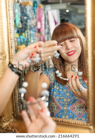 Woman is choosing necklaces in a accessory shop - stock photo