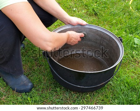 Woman is cleaning big greasy kettle with metal wire wisp outdoor on green grass.