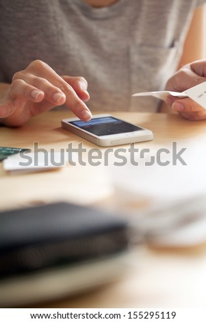 Woman is counting money on her phone while holding a cheque. There is also a leather wallet close to the camera - stock photo