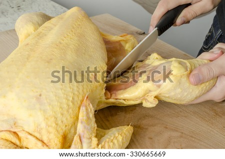 Woman is cutting free-range chicken on wood board in a kitchen.