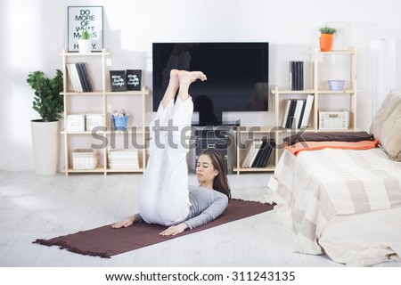 Woman is doing fitness at home on her living room floor.Fit woman doing yoga on mat at home in the living room - stock photo