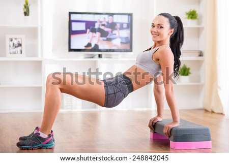 Woman is doing fitness at home on her living room floor while watching and participating in a class - stock photo