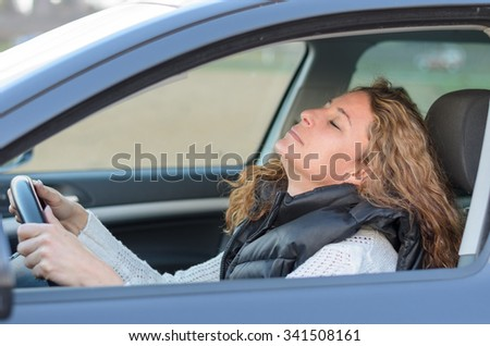 woman is driving her car and is falling to sleep
