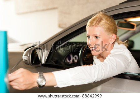 Woman is driving out of a parking garage and is slipping the ticket into the barrier of the garage - stock photo