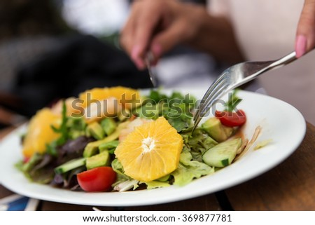 woman is eating a fresh salad in a restaurant - stock photo