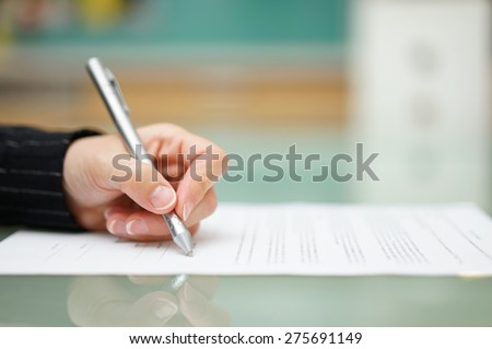 woman is filling document on glass table, shallow depth of field - stock photo